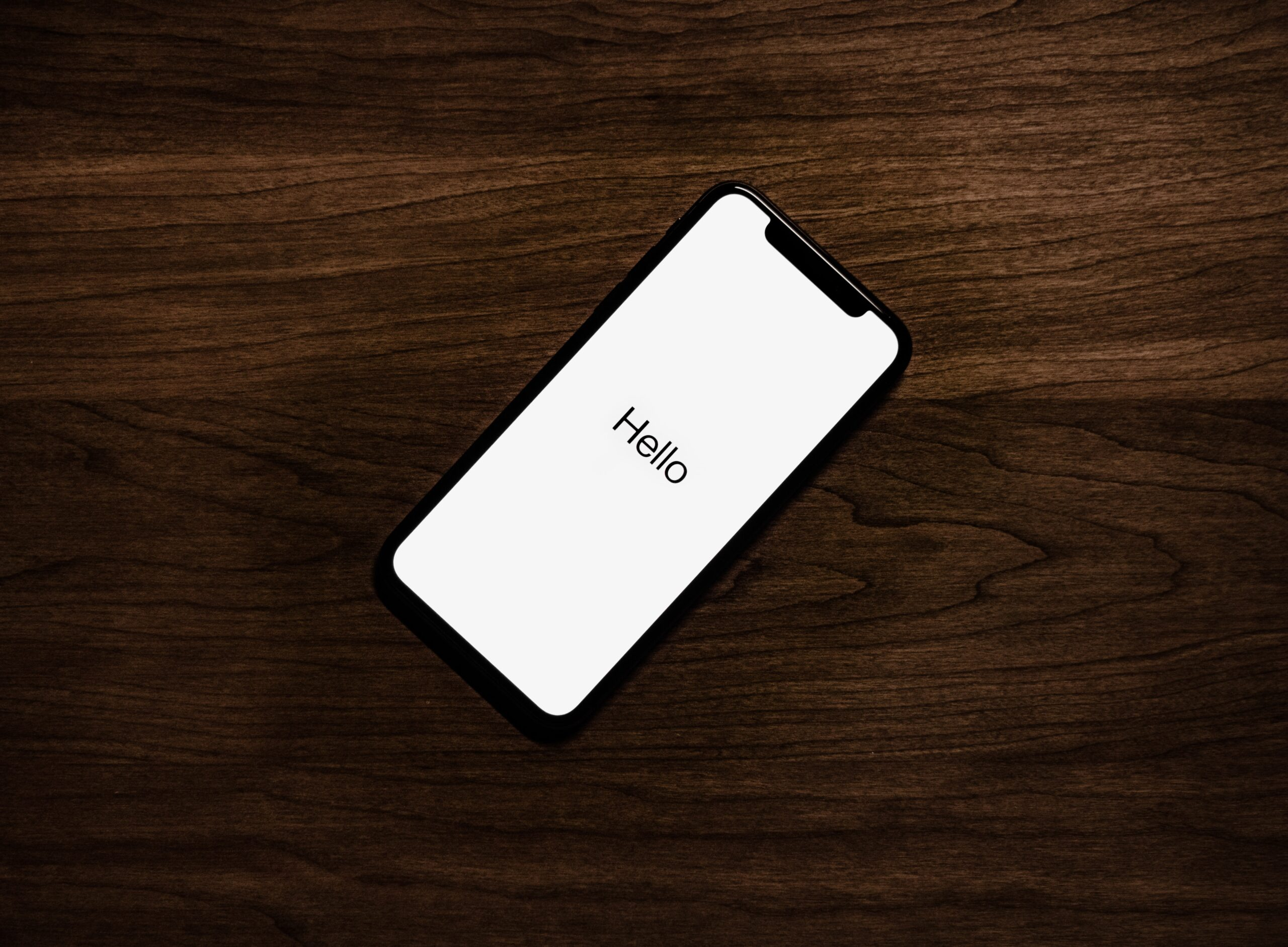 iphone on table with hello message